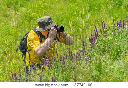 Enthusiastic mature photographer taking a photo of wild nature