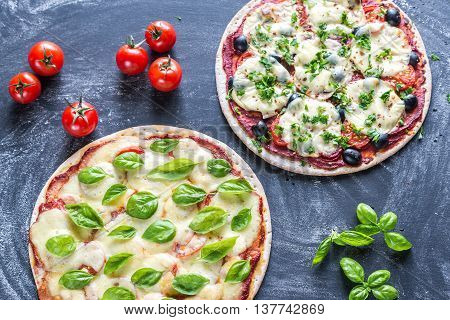 Two Pizzas With Ingredients On The Wooden Background