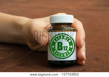 Human Hand Holding A Bottle Of Pills With Vitamin B12