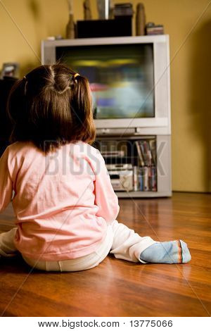 Rear view of little girl sitting on the floor and watching cartoons on TV at home