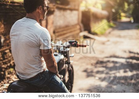 Rear view shot of young man sitting on his motorcycle and looking away.
