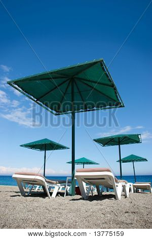 Photo of deck-chairs under umbrellas on seashore with water near by