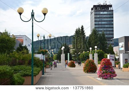 Povazska Bystrica, Slovakia - July 8, 2016: People in town centre enjoy nice day high Administrative building of state agencies in background
