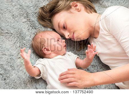 Two Sisters. Older Sister Kid Hugging His Newborn Little Sister.