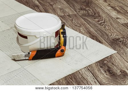 Tool and a container of glue for laying linoleum flooring.