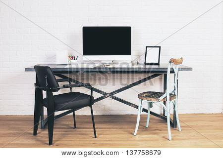 Modern black chair and creative blue chair at designer desk with blank computer screen and frames. Mock up