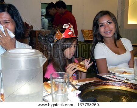 CEBU CITY, CEBU / PHILIPPINES - AUGUST 12, 2011: A girl wears a crown while eating pizza at the Pizza Hut in the SM City Cebu shopping mall.