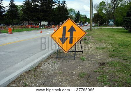 PLAINFIELD, ILLINOIS / UNITED STATES - MAY 4, 2016: A yellow sign cautions drivers of two-way traffic in a construction zone on Renwick Road in Plainfield.