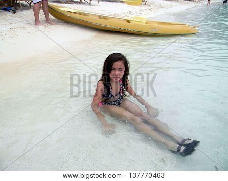 LAPU LAPU, CEBU / PHILIPPINES - JULY 28, 2011: A girl sits in the water at the beach of Shangri-La's Mactan Resort and Spa.