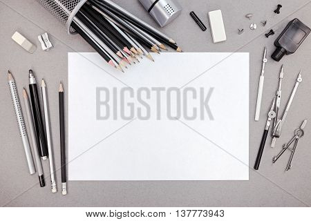 Designer Workspace With Blank Paper, Pencils And Various Drawing Tools