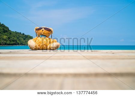 Brown cutie bear doll wear sun glasses sit on wooden floor looking up to the sky - getaway concept