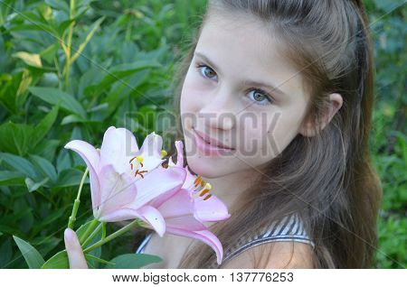 The young girl on nature with a bouquet of pale pink lilies