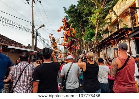 KUTA, INDONESIA - MARCH 08: Tourists take photo of the Ogoh-ogoh statues at the parade on the eve of Nyepi day on March 08 2016 in Kuta Bali Indonesia