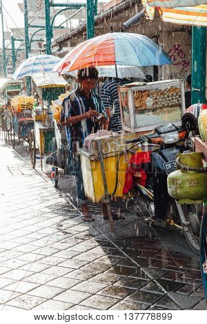UBUD, INDONESIA - MARCH 08: Indonesian food vendor hides from the rain under umbrella of his stall on the street of Ubud Bali Indonesia on March 08 2016