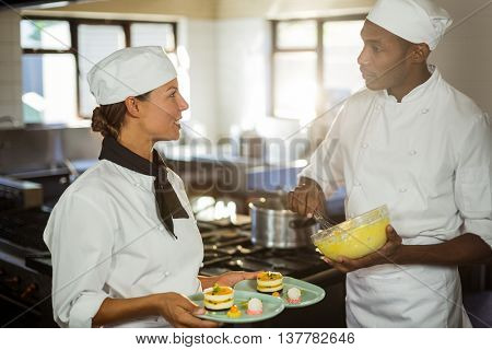 Two chefs talking to each other while working in kitchen