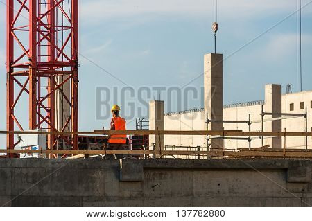 Crane and unfinished building construction and one workman