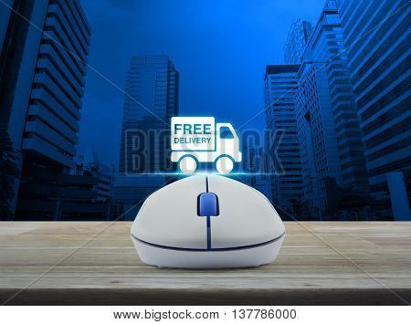 Wireless computer mouse with free delivery truck icon on wooden table in front of city tower background Transportation business concept