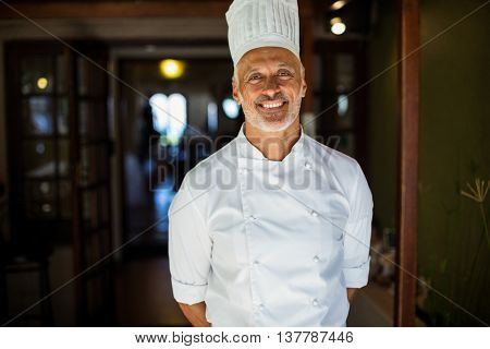 Portrait of chef standing with hands behind back in restaurant