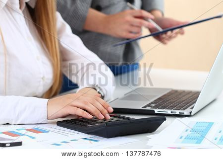 Two female accountants counting on calculator income for tax form completion hands closeup. Internal Revenue Service inspector checking financial document. Planning budget audit insurance concept