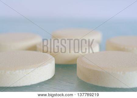 Soluble tablets on glass table top closeup. Shallow depth of field.