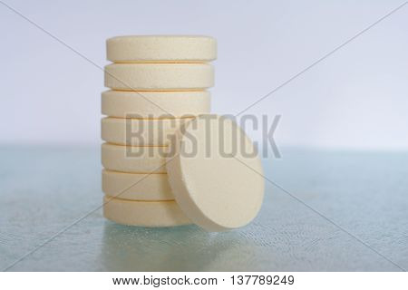 Pile of soluble tablets on glass table top closeup. Shallow depth of field.