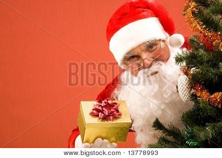 Photo of happy Santa Claus with small giftbox looking at camera out of decorated xmas tree