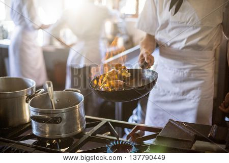 Mid section of chef tossing stir fry over large flame in commercial kitchen