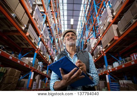 Low angle view of worker is smiling and holding a clipboard in a warehouse