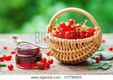 Basket Of Red Currant Berries And Jar Of Redcurrant Jam On Table Outdoors