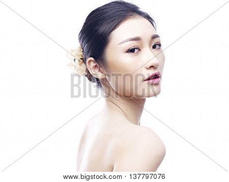 studio portrait of a young and beautiful asian woman side view looking at camera isolated on white background.