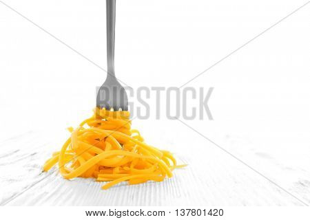 Fork with cooked pasta on white background