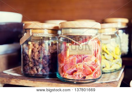 food, storage and eating concept - close up of jars with dried fruits at grocery