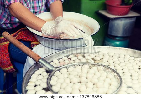 cooking, asian kitchen and food concept - close up of cook frying meat or rice balls in oil at street market