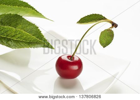 Fresh red cherry with leaf on a white background close up
