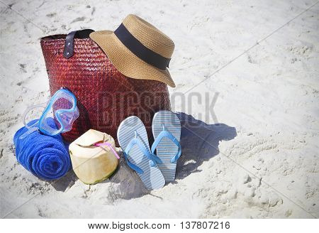 Straw hat wather mask beach towel flip flops with beach bag and coconut cocktail. Summer travel and vacation concept