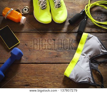 Female sport equipment on a wooden background. Sports items: sneakers clothing bottle of smoothie dumbbell and mobile phone on the wooden background. Set for sports activities in the gym