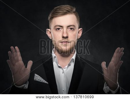 Man covering his ears over dark background.