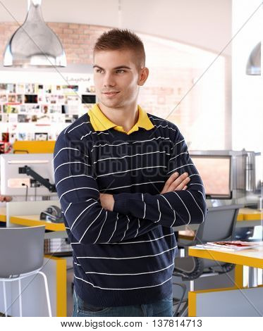Young casual caucasian business startup office worker standing arms crossed, smirking, looking away, standing.