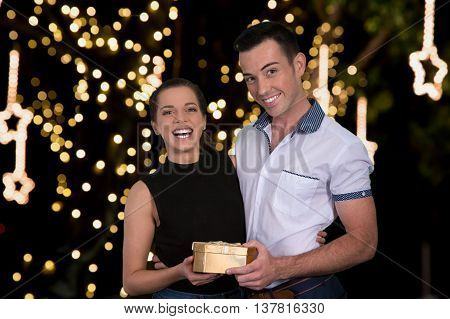 Gorgeous young couple with a boxed gift and lights in the background