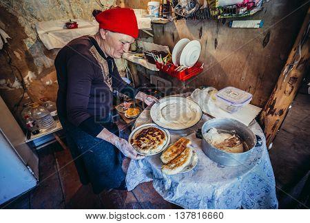Upper Svanetia Georgia - July 24 2015. Old woman makes khachapuri and lobiani in small bar halfway between Mestia and Ushguli community