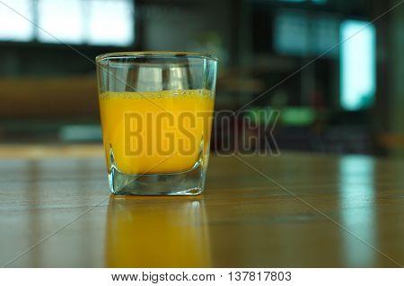 glass of orange juice on wood table
