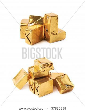 Pile of multiple bouillon stock broth cubes wrapped in golden foil, composition isolated over the white background, set of two different foreshortenings
