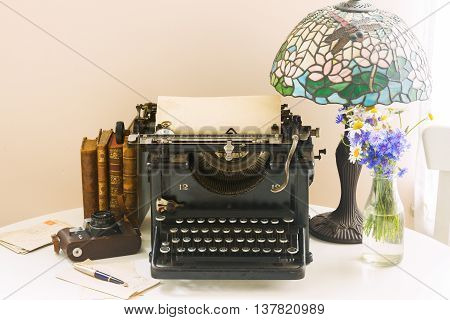black vintage typewriter with books on wooden table with art nuveau lamp