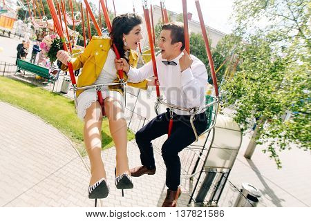 Emotional newlyweds laughing while riding on high carousel in amusement park. Expressive wedding couple at carnival.
