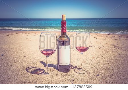 A Bottle Of Wine And Glasses On The Beach