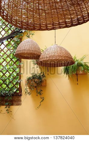 Mediterranean terrace design. Wicker lamps, light wickerwork willow and green plants yellow wall background