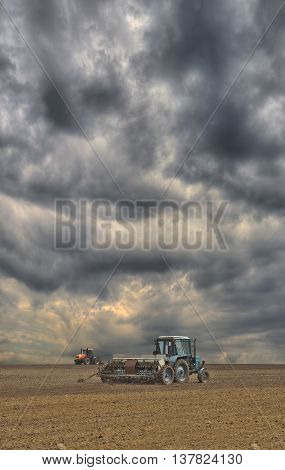 Tractors sowing the field with the seeder with dramatic sky on the background
