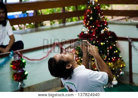 Koh Samui, Thailand - December 14 : guy is a snake handler in the arena of kissing a Cobra for the entertainment of tourists on the Day of St. Lucia, December 14, 2012.