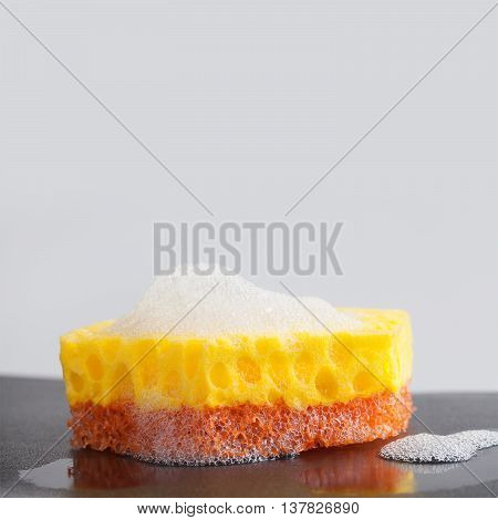 Colorful cleaning sponges with soap suds foam. Cleaning supplies concept. copy space,