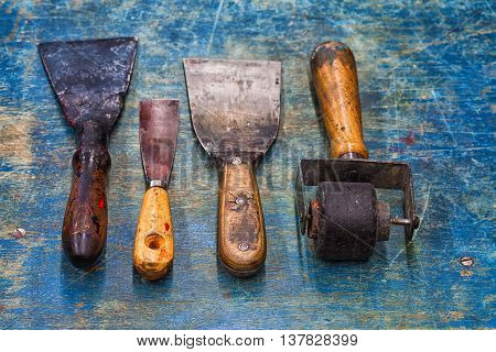 Shabby and used artist tools: black rubber roller, big and small putty knives on blue paint wooden background. Diy accessories, decorator concept. soft focus